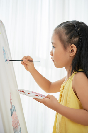 Little talented Asian girl concentrated on painting